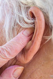 Senior woman inserting hearing aid in her ears Royalty Free Stock Images