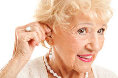 Senior Woman Inserts Hearing Aid. Closeup of a senior woman inserting a hearing aid in her hear. Focus on the hearing aid stock photo