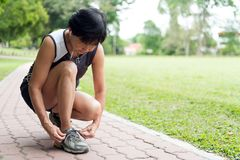 Senior jogger tighten her running shoe laces. Senior woman jogger tighten her running shoe laces Royalty Free Stock Photo