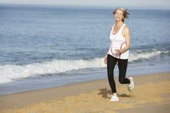 Senior Woman Jogging Along Beach Stock Photo
