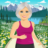 Senior woman jogging among beautiful mountains and field of daisy flowers Stock Photography