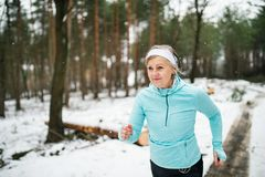 Senior woman jogging in winter nature. Senior woman jogging outside in winter nature royalty free stock photography