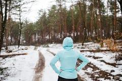 Senior woman jogging in winter nature. Senior woman jogging outside in winter nature, resting. Rear view Stock Photography