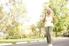 Senior Woman Jogging In Park. Senior African American Woman Jogging In Park royalty free stock images