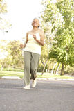 Senior Woman Jogging In Park Stock Photography