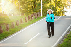 Senior Woman Jogging at the Pedestrian Walkway. 70 years old Senior Woman Jogging at the Pedestrian Walkway in the Bright Autumn Evening Royalty Free Stock Images