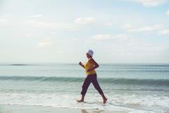 Senior woman jogging on sea beach Stock Photos