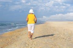 Senior woman jogging on sea beach. At the morning, back view Royalty Free Stock Image