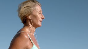 Senior woman jogging on a sunny day listening to music stock footage