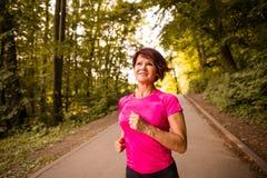Senior woman jogging. Vital senior woman jogging in park on summer evening stock images