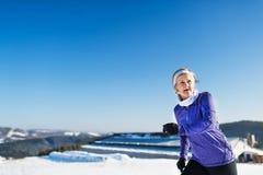 Senior woman jogging in winter nature. Copy space. stock photos