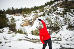 Senior woman jogging in winter nature. Senior woman jogging outside in winter nature, stretching. Rear view Royalty Free Stock Photography