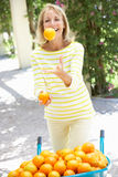 Senior Woman Juggling Oranges By Wheelbarrow Royalty Free Stock Images