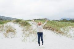 Senior woman jumping at the beach Stock Photo