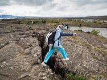 Senior woman is jumping over an earth gap at Thingvellir Nationa Royalty Free Stock Photography