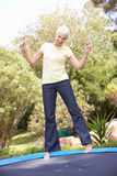 Senior Woman Jumping On Trampoline In Garden Royalty Free Stock Photo