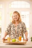 Senior woman keeping diet. Senior woman holding a tray with diet food, orange juice, fruit, tea and yogurt Stock Image