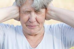 Senior woman keeps her ears shut Royalty Free Stock Image