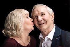 Senior woman kissing happy man on black stock photo