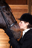 Senior woman kissing her horse Stock Images