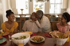 Senior woman kissing senior man while having meal on dining table. Front view of African American senior women kissing her husband surrounded by his daughter and stock photo