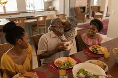 Senior woman kissing senior man while having meal on dining table. Side view of African American senior women kissing her husband surrounded by his daughter and stock photos