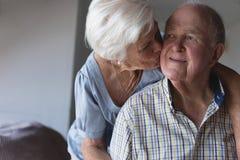 Senior woman kissing senior man at home. Front view of an active senior women kissing senior men on the cheek at home stock photography
