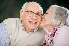 Senior Woman Kissing On Man's Cheek Stock Image