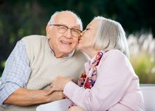 Senior Woman Kissing On Man's Cheek. Senior women kissing on man's cheek while sitting at nursing home porch Royalty Free Stock Photo