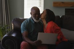 Senior woman kissing senior man while using digital tablet in living room at home. Front view of active senior women kissing senior men while using digital stock photo