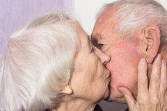 The senior woman kissing old man stock photos