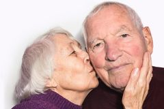 The senior woman kissing old man stock photography