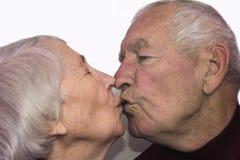 The senior woman kissing old man. Beautiful senior women kissing happy men isolated on whita royalty free stock image