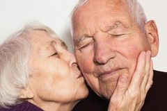 The senior woman kissing old man stock images
