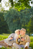 Senior woman kissing old man during picnic Stock Photo