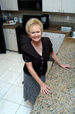 Senior woman in kitchen Stock Photography