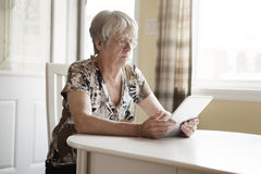 Senior Woman at the Kitchen, Holding a Tablet Stock Photos