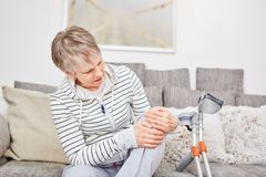 Senior woman with knee injury. Has pain and uses crutches stock photos