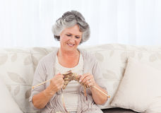 Senior woman knitting on her sofa Royalty Free Stock Photos