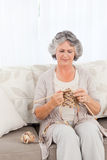 Senior woman knitting on her sofa Royalty Free Stock Images