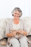 Senior woman knitting on her sofa Stock Photography