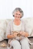 Senior woman knitting on her sofa Stock Photography