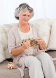Senior woman knitting on her sofa Stock Photos