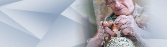 Active elderly woman. panoramic banner. Senior woman knitting at home. panoramic banner royalty free stock image