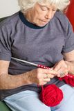 Senior Woman Knitting With Red Wool Royalty Free Stock Images