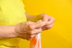 Senior woman knitting a scarf at home Royalty Free Stock Image