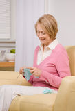 Senior woman knitting on sofa at home Stock Photography