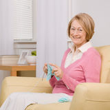 Senior woman knitting on sofa at home Stock Photos