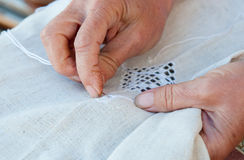 Senior Woman knitting a white fabric cloth Royalty Free Stock Image
