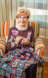Senior woman knitting a wool quilt with patches Royalty Free Stock Image